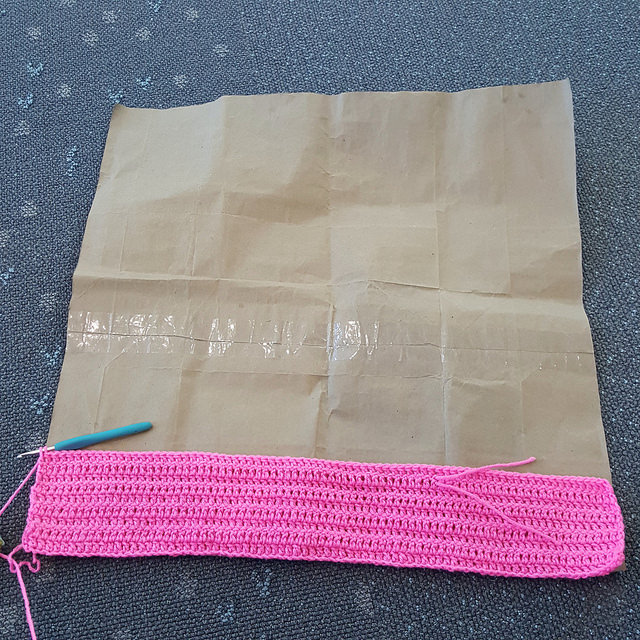 I measure a future orange and pink double crochet square on a template