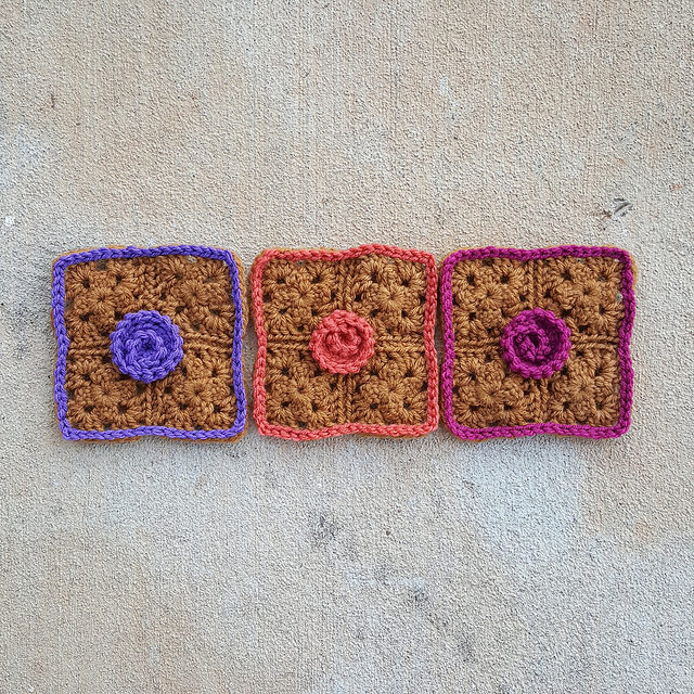 three five-inch crochet squares with a crochet flower applique