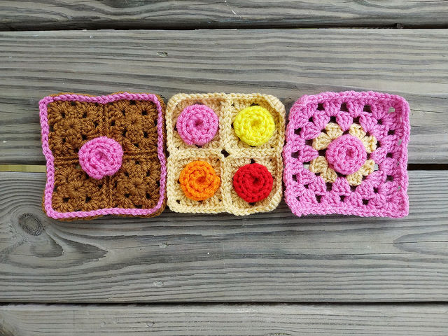 Three four-patch granny squares with crochet roses
