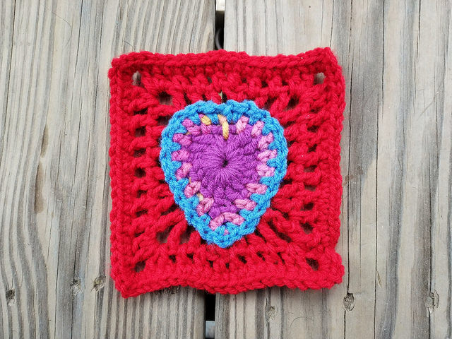A five-inch rehab crochet square with boho crochet heart center