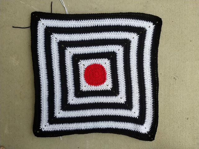 A sixteen round black and white striped granny square baby blanket with a red crochet circle at the center
