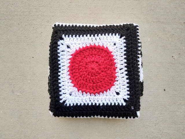 a red crochet circle centered black and white striped granny square baby blanket