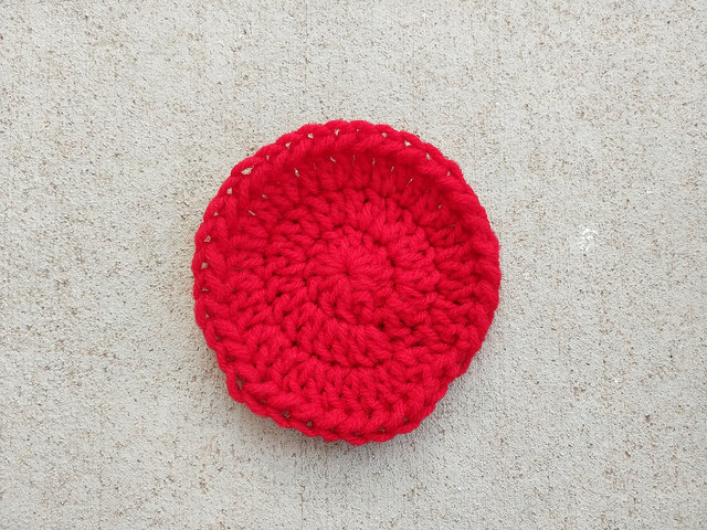 A red three round double crochet circle with a half double crochet edge