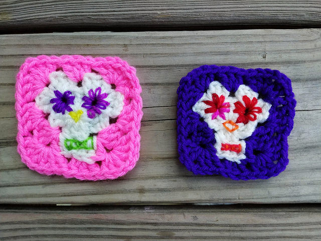 Two Day of the Dead granny squares ready for a final crochet rehab after threading the needle and decorating them