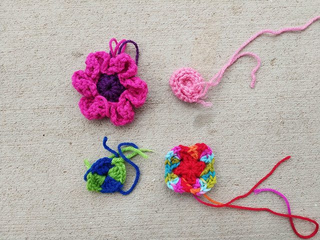 Four crochet remnants (including a flower and a rose) ready for crochet rehab