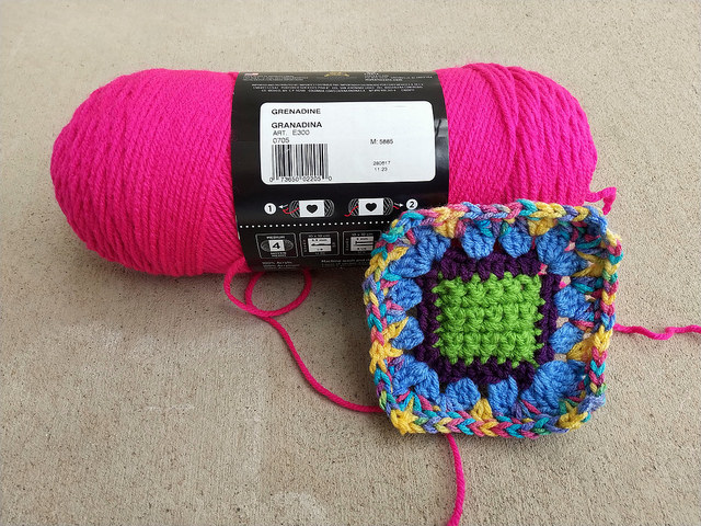 a crochet square to be rehabbed posing with the yarn for the final round
