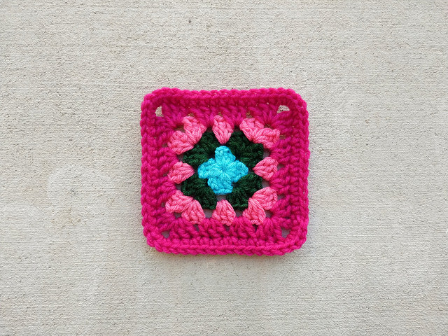 The previously one-round granny square transformed into a five-inch crochet square