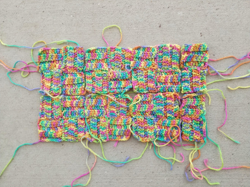 Twenty-eight lightly textured crochet remnants in the process of being transformed into five-inch four-patch crochet squares