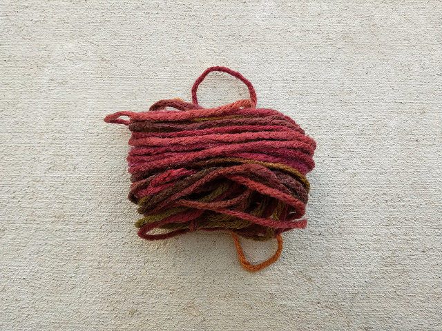 An unwisely long length of Cherry Coke worsted weight yarn