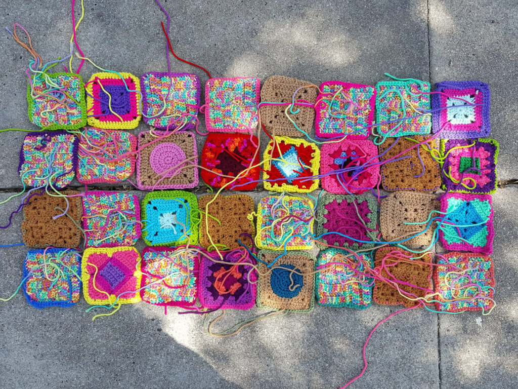 Thirty-two rehabbed crochet squares with the ends woven in