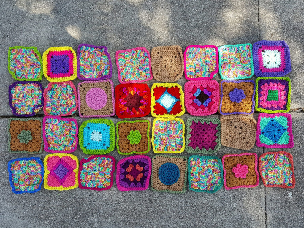 Thirty-two rehabbed crochet squares ready for adventure