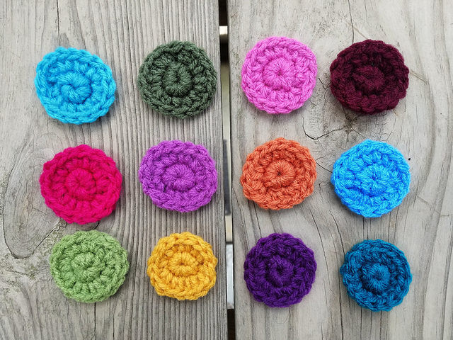 A pile of twelve crochet circles for the center of twelve crochet squares