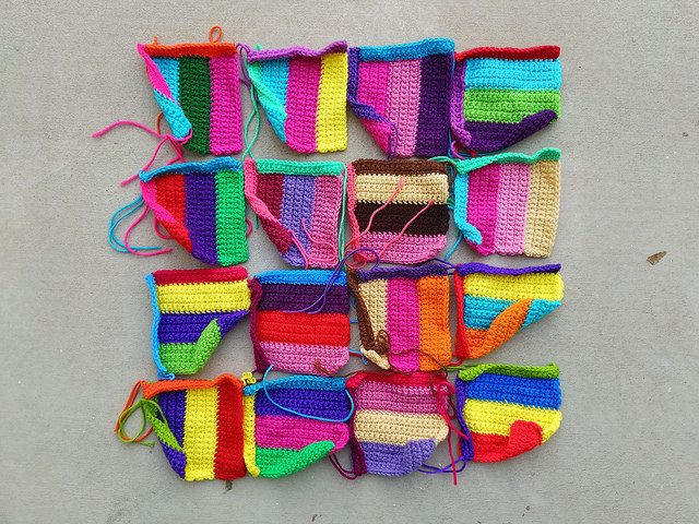Sixteen rehabbed television test strip crochet squares in need of finishing work