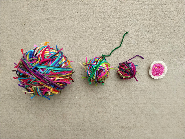 Three balls of yarn scraps with a four-round crochet cookie for scale