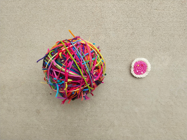 Three scrap yarn balls wound into one with a four-round crochet cookie for scale
