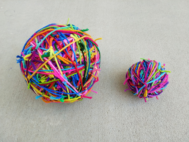 The three balls of yarn scraps (on the right) wound into one ball and ready to be joined to the main magic scrap yarn ball