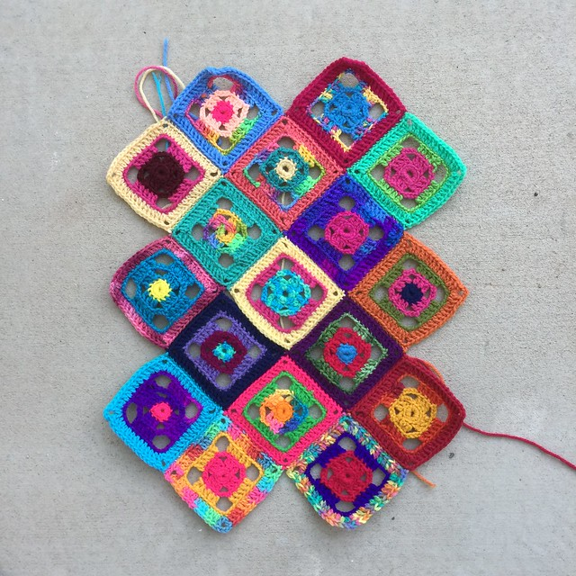 The seventeen four-inch flamboyant granny squares all laid out and ready to go
