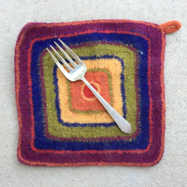 A large serving fork with four prongs to use as a tool to make a flower with yarn