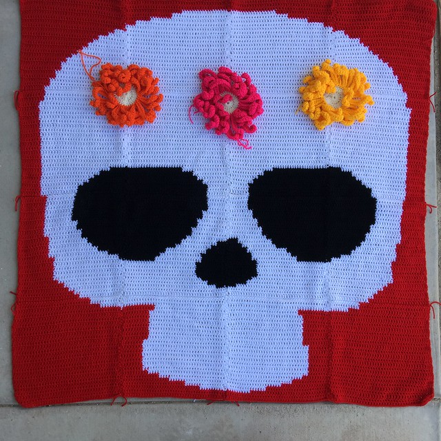 A Day of the Dead crochet yarn bomb with three large crochet flowers