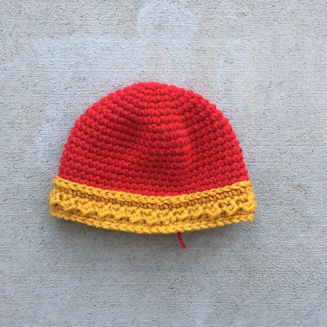 A red crochet hat with a textured crochet gold headband