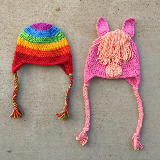Two crochet hats for a toddler--one rainbow hat and one pink and light orange llama hat.