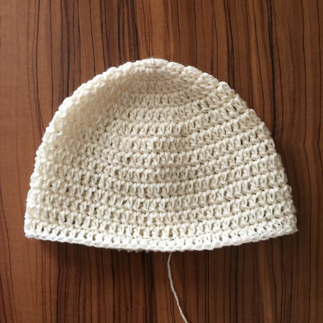 The start of a crochet llama hat worked in double crochet with off-white yarn