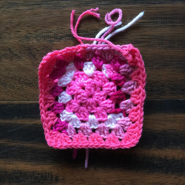 The start of a pink scrap yarn granny square