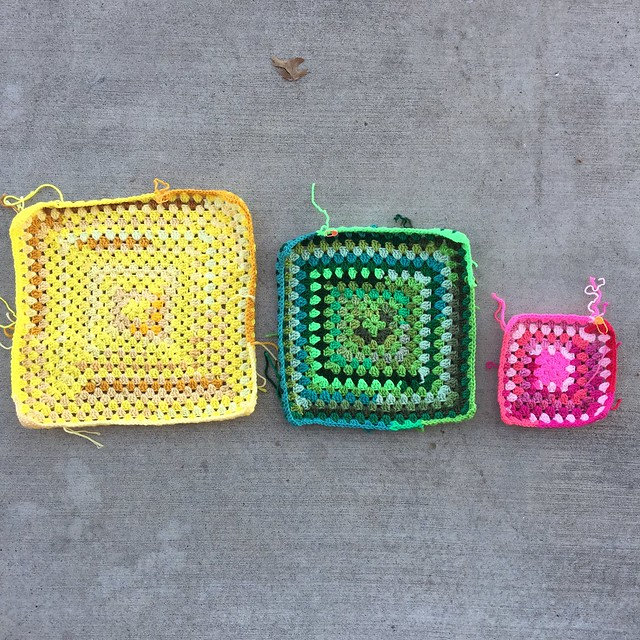 Three scrap yarn granny squares worked in yellow, green, and pink.