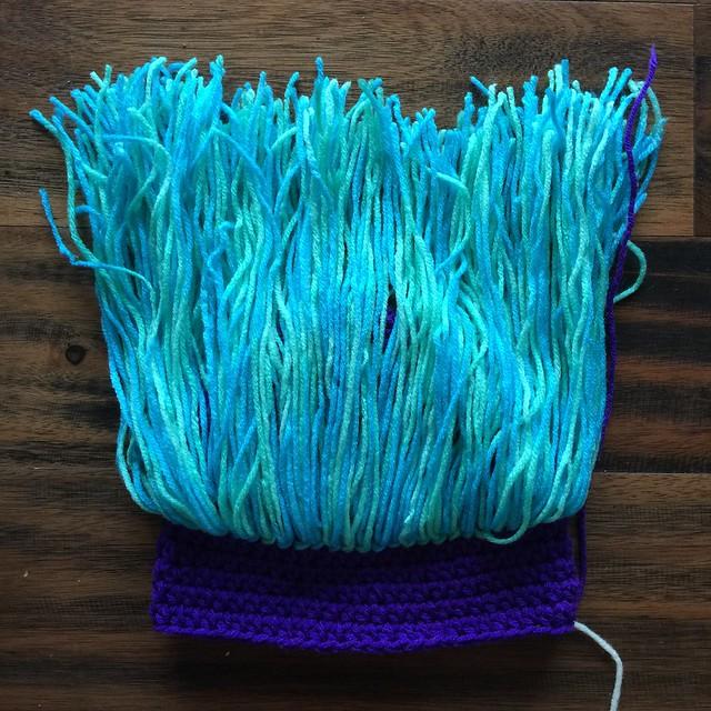 I attach yarn hair to a crochet troll hat on a busy crochet weekend
