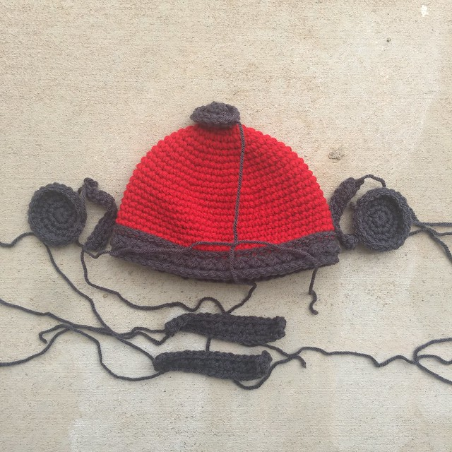 A future cherry red crochet viking helmet for a baby with charcoal embellishments