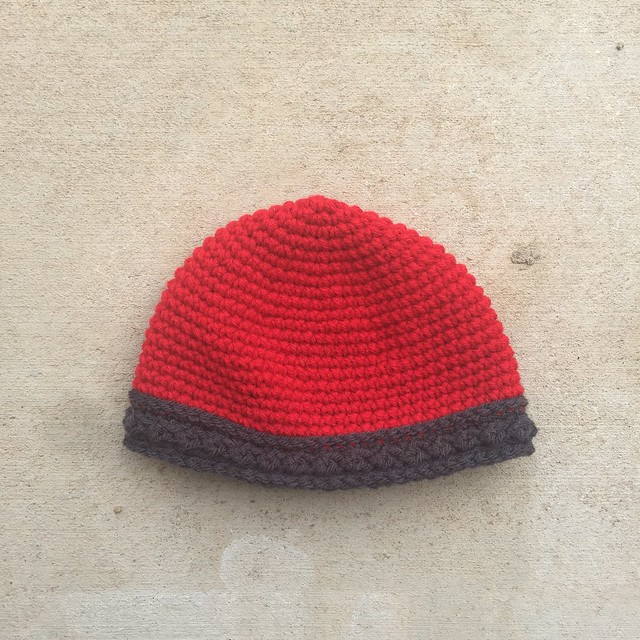 Crochet rescue in the form of a  cherry red crochet viking helmet for a baby
