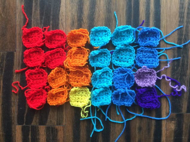 Twenty-four crochet solving squares made in a  rainbow of colors