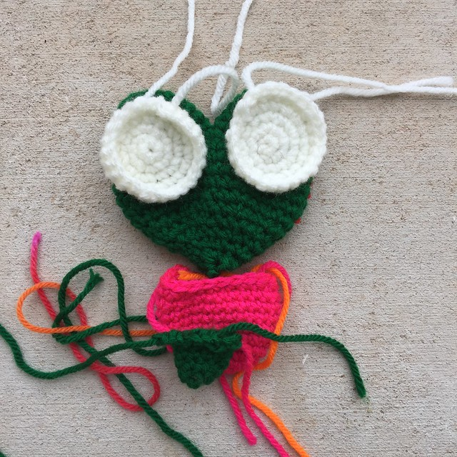 An amigurumi frog made with dark green and grenadine pink yarn