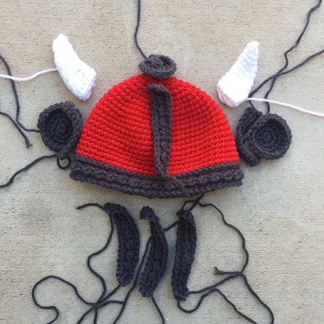 A red and gray crochet Viking helmet for a baby