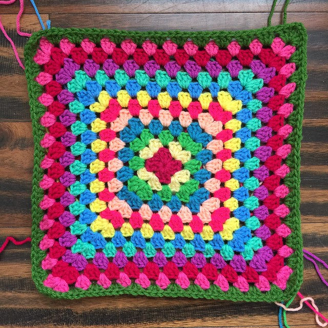 The thirteen round of what will be a thirty-six ground great granny square blanket worked in a myriad of colors