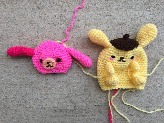 A not quite finished pink crochet sugarbunny and yellow crochet dog.