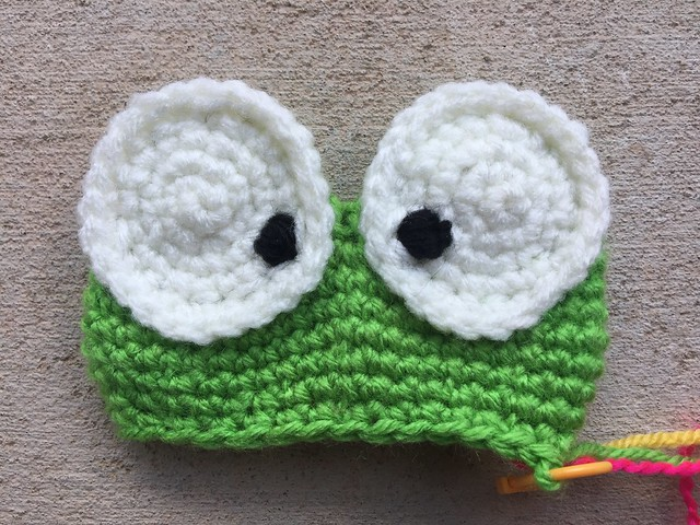 Two recently appliquéd crochet frog eyes gazing out at the world