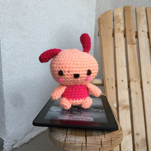 A crochet Pochacco, sitting on a kindle, worked in light coral, rouge, and grenadine yarn.