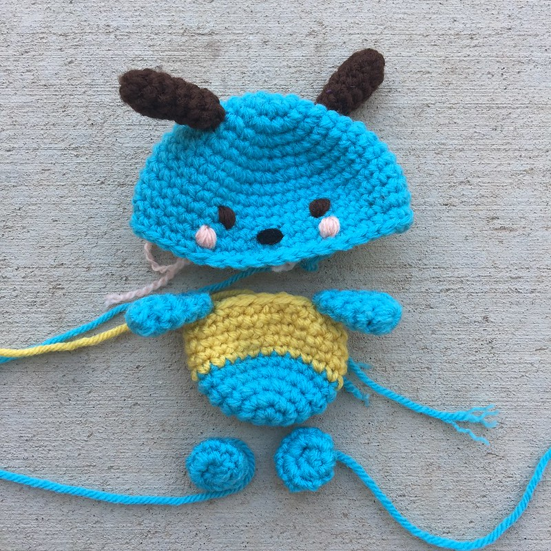 A Hello Kitty crochet Pochacco worked in turquoise, brown, and yellow yarn
