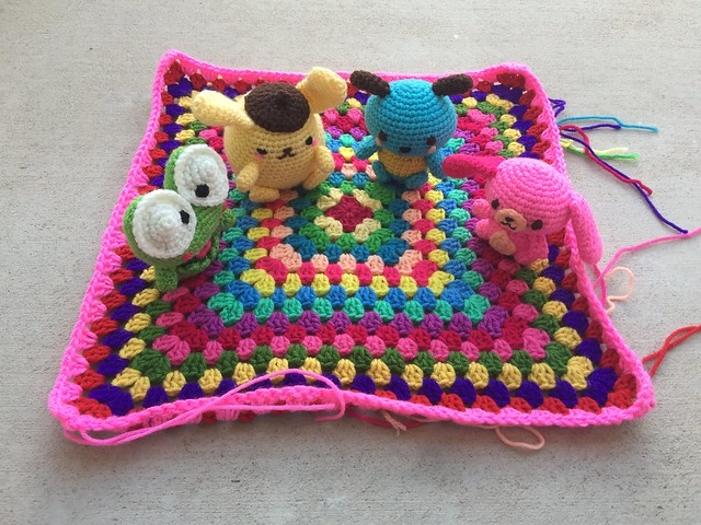 Four crochet Hello Kitty characters sitting on a granny square blanket on a blustery crochet day