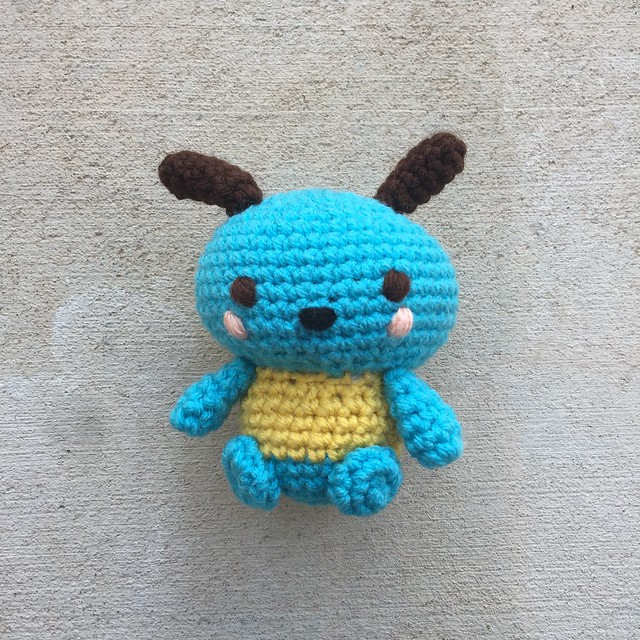 A turquoise crochet Pochacco with brown ears, peach cheeks, and a yellow sweater.
