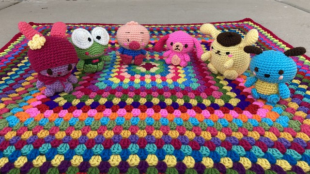 Six amigurumi ready for a picnic on a multicolor granny square blanket