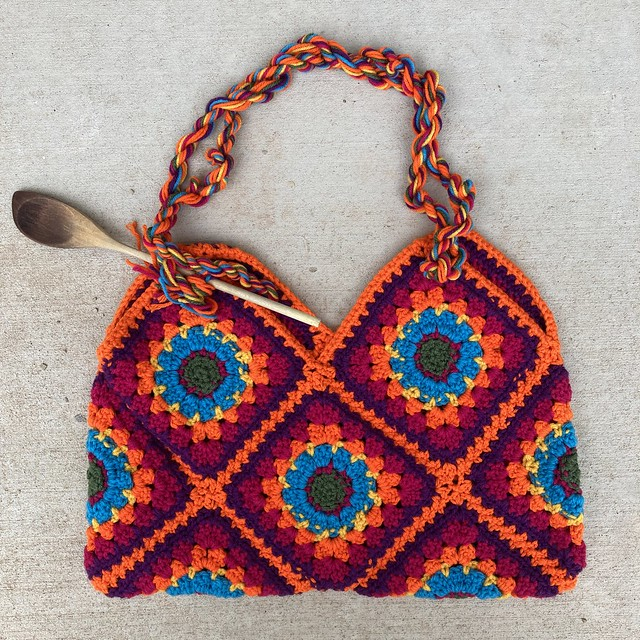 A psychedelia granny square purse with one of the twisted yarn rope straps almost completed