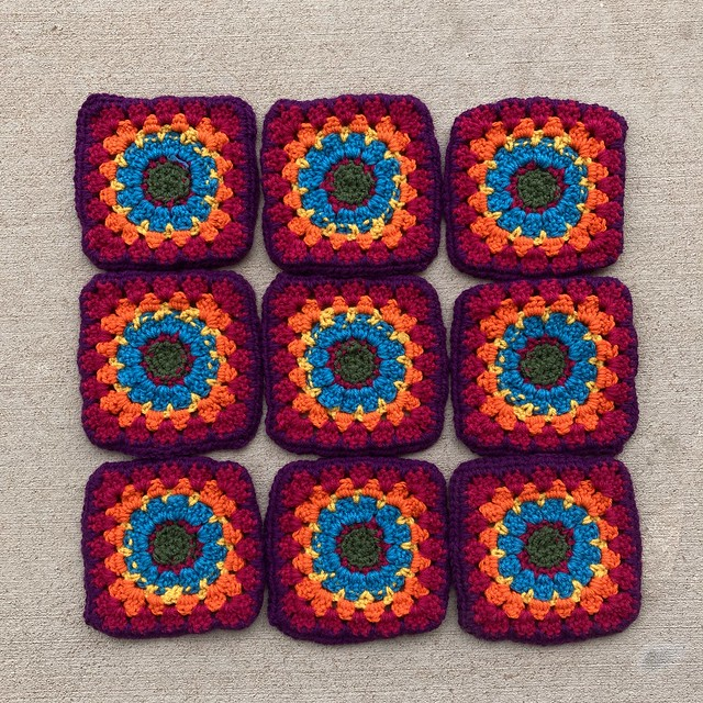 The back of a nine patch of multicolor granny squares with the ends woven in and trimmed