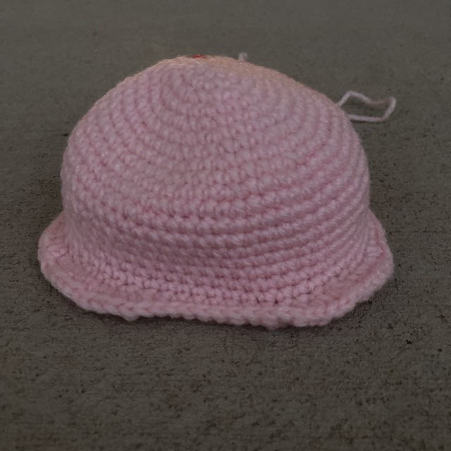 The nineteen rounds of a crochet skull worked in baby pink