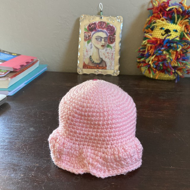 A future pink crochet skull in the foreground with a tin painting of Frida Kahlo and a scrap yarn kitty in the background