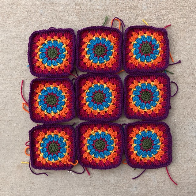 Nine crochet squares ready to have the ends woven in and trimmed