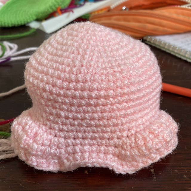 A pink crochet skull with a nearly completed brow