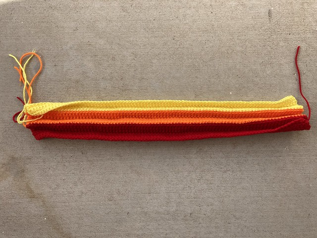 Three color strips of a future crochet purse, folded into pleats