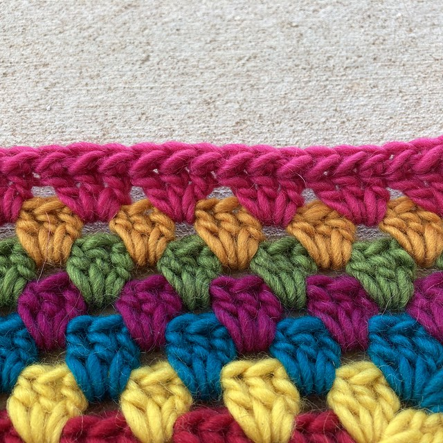 A detail of the back side of a half-double slip stitch used to edge a crochet rug